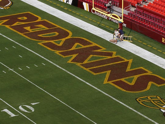 Groundskeepers prepare the end zone for the NFL football preseason game between the Washington Redskins and the New England Patriots in Landover, Md.