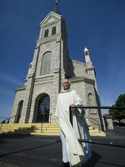 "Father Joe Coerber stands outside St. John the Baptist Church in Johnsburg. He plans to ""semi-retire"" after 49 years of service to Catholic communities."