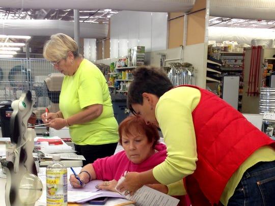 Volunteers discuss the amount of pet food left during