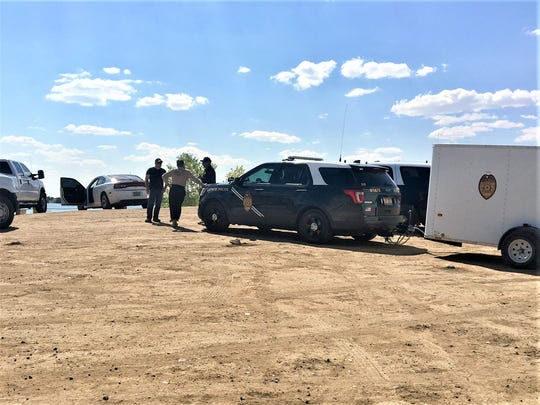 State police officers and members of the recovery team prepare to leave Farmington Lake on Saturday, Sept. 2, after finding the body of 31-year-old drowning victim Jamie Tolbert.