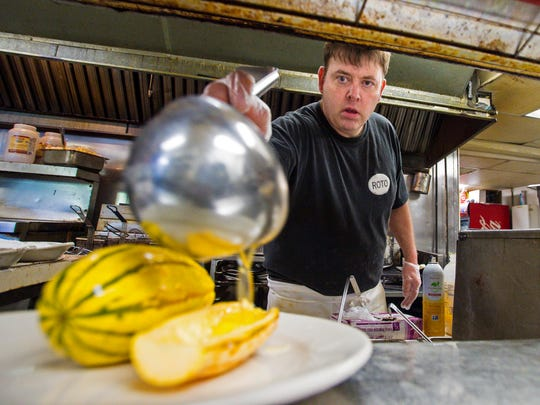 Owner and chef Brendan McGrath pours butter over roasted delicata squash at The Rotisserie in South Burlington on Tuesday, October 17, 2017.