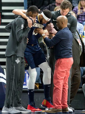 New Orleans Pelicans forward Anthony Davis (23) is helped up off the court after being injured during the second half against the Utah Jazz at Vivint Smart Home Arena.