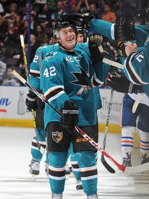 Livonia native Bryan Lerg is congratulated by his San Jose Sharks teammates after scoring a goal in his first NHL game April 9.