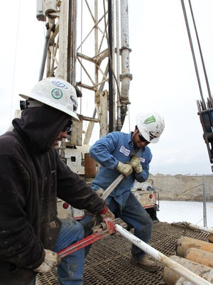 Workers drill for water for a farmer near Bakersfield in February 2014.