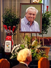 A set of golf clubs and a photo of golfer Arnold Palmer sit in the Basilica at St. Vincent's College in Latrobe, Pa., for a memorial service Tuesday, Oct. 4, 2016.