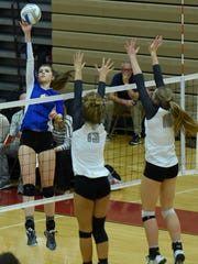 Marian's Lauren Wenzel (6) makes a kill goes high for a kill shot over Novi defenders Jaeda Porter (13) and Ally Cummings (16).