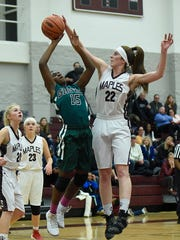 Seaholm's Dana Hoerman (right) blocks a jump shot  by Groves' Lauren Palmer.