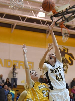 North Farmington's Sam Cherney (right) works inside for a first-quarter layup during Tuesday's victory over Rochester Adams.