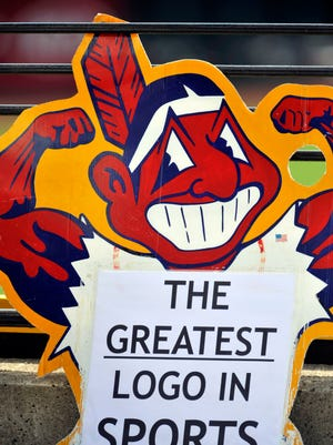 A fan holds up a Chief Wahoo sign.