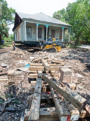Workers from Ducky Johnson House Movers move the historic house from its original foundation at 422 W. Gregory Street in Pensacola on Friday, July 21, 2017.