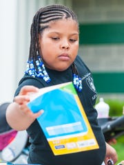 Jayla Evans, 8, pulls out a book during Vineland School District's book giveaway at the Vineland School District Warehouse on Wednesday, August 30.