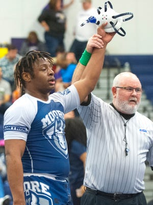 In the 220 lb. weight class championship match, Damoreon Travis of Moore has his hand raised in victory by the referee. Feb. 10, 2018