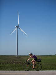 Andrea Parrott, RAGBRAI merchandise and media manager, rides past a wind turbine outside Ogden in 2018.