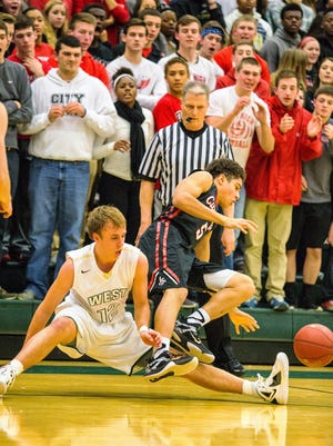 Iowa City West's Alex Henderson (12) and Iowa City High's Naeem Smith (5) get tangled up going for the ball during the first half of play at Iowa City West on Friday, February 13, 2015.