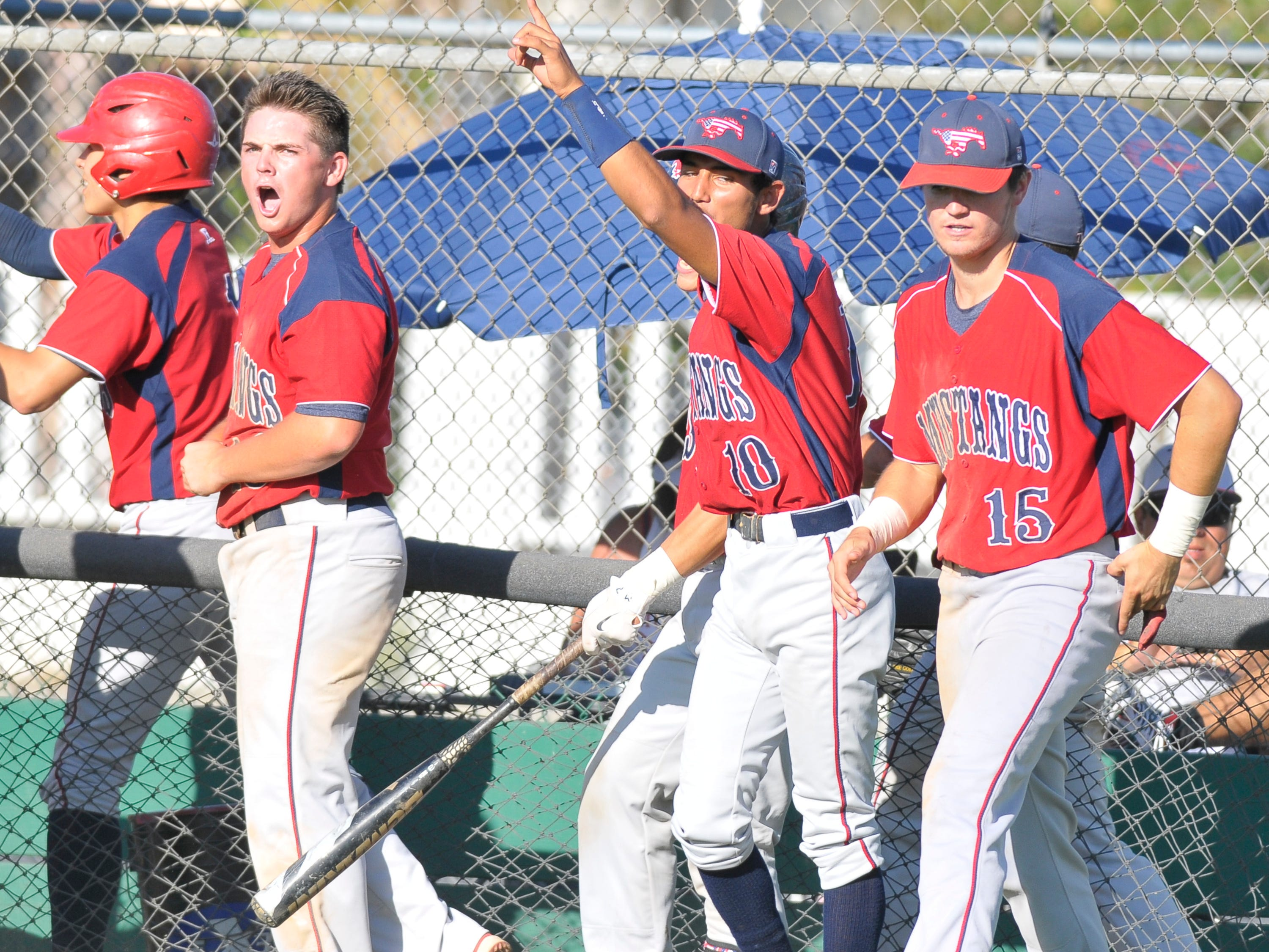 Tulare Western players celebrate after a run scores for the Mustangs during their 6-1 win over Porterville on Tuesday.