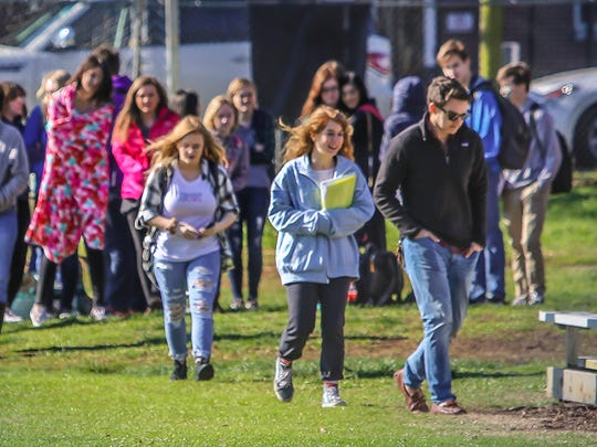 Students Jacob Heinrich and Jayda Tiano lead their peers to the soccer field where they gathered outside Central Magnet School on Wednesday morning as part of the National School Walkout.