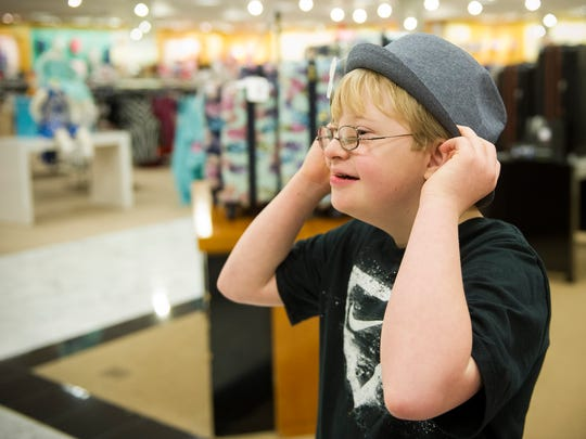 Layton Sauls, 11, of Carmi, Illinois, tries on a fedora while shopping for clothes for A Night of Stars & Styles fashion show, at Dillard's in Evansville.