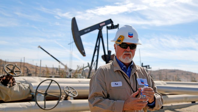 Pat Young, facilities operations foreman for Chevron, explains how oil is pumped out of the ground during a recent tour of the San Ardo Oil Field in south Monterey County.