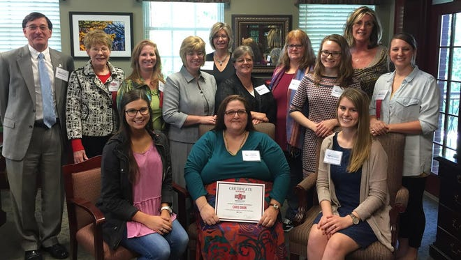 The Women's Business Leadership Center awards its founding class scholarships and certification of recognition during a luncheon at Arkansas State University-Mountain Home Tuesday: (Front) Brooke Barnes, Christina Dixon and Sydney Wendfeldt; (back) Robin Myers, Kathy Loyd, Charlotte Razer, Katy Page, Karen Heslep, Lindy Barclay, Ethel Still, Rebekah Oliger, Kim Worlow and Tera Payne.