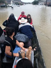 A family is taken from a flooded neighborhood in Taylor Moore's boat. Moore, from Ruby, and a group of friends helped rescue victims of Hurricane Harvey in East Texas over several days.