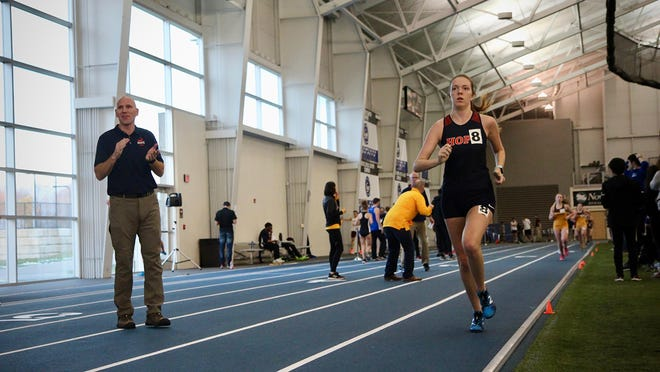 Kevin Cole (left) cheers on Jacinda Cole at an indoor track and field meet.