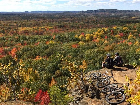 Mountain bikers rest at an overlook at Levis Mound