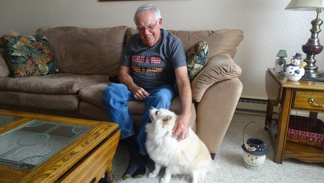 Randy Albertson, 65, credits a friend with saving his life by applying CPR after his heart stopped on the golf course this past August. Here, he shares a moment with his dog Zoey.