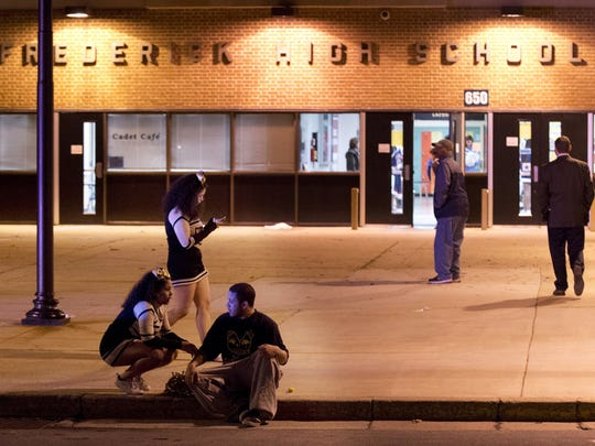 People gather outside the entrance to Frederick High School following a shooting in Frederick, Md., Wednesday, Feb. 4, 2015. Police and school officials said students were shot outside the school while a basketball game was being played inside.