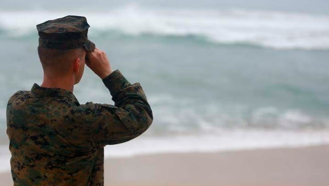 A Marine Officer uses binoculars to search for debris of a helicopter mishap in Haleiwa Beach Park, on Jan. 15, 2016. A Marine died early Saturday morning after the boat he was in capsized in waters near the Marine Corps Base Hawaii.