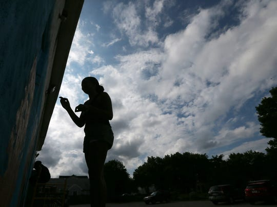 Kaori-Mei Stephens, 17, works on her portrait under a cloud filled night sky as a trio of Rochester teen girls paint a large mural on the side of the Flying Squirrel at 285 Clarissa St. as part of Wall\Therapy 2017.