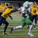 Novi's Nathan Hankerson, left, dashes past a couple of South Lyon Lions on Sept. 23 on his way to a touchdown. Lion Danique Lewis (#4) gives chase.