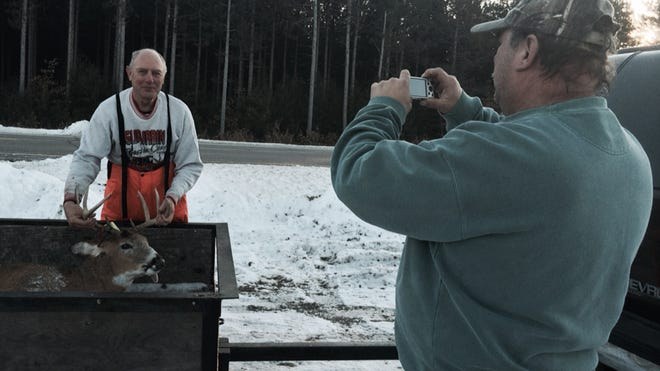 Bob Lucht takes a photo of Richard Nina of Almond with the buck he registered at Hideout II in Amherst for the bar's hunting album on Sunday, November 30, 2014.