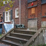 Nancy Irizarry stands beside the abandoned property that neighbors her Rand Street home in Camden on Wednesday, October 16, 2014. The property is one of thousands in the city that has been slated for demolition, but never followed through on.