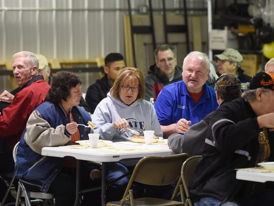 Area bus drivers enjoy a waffle breakfast as part of