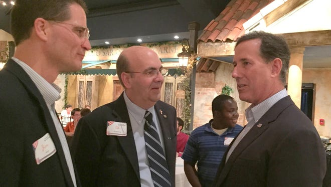 Rick Santorum, right, talks Thursday night with Jim Koch, far left, and Al Ringgenberg, both of Council Bluffs, during a campaign appearance in rural Glenwood.