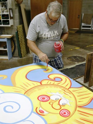 Cartoonist Tim Decker works on a mural at RCS Empowers in Sheboygan that is being designed to honor the organisation's 60th year. It will be unveiled during a celebration Sept. 22, 2015.