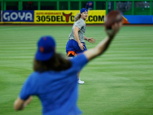 New York Mets' Jacob deGrom, foreground, throws a football to Noah Syndergaard, during warmups before a baseball game against the Miami Marlins, Sunday, April 16, 2017, in Miami. (AP Photo/Wilfredo Lee)