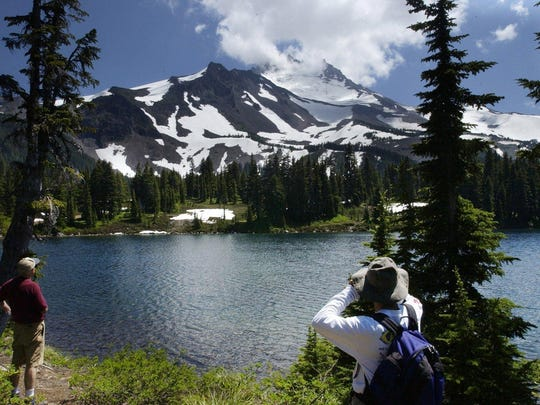 Hikers look out at Mount Jefferson on Scout Lake in the Jefferson Park Wilderness.