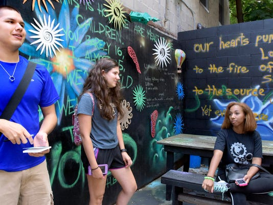 York College freshmen, from left, Esdras Moore of Dallas, PA; Sarah Rodriguez of Bethlehem and Savannah Ruiz of New York City, sit in the Poetry Garden in Royal Square recently. They and other Graham Innovation Scholarship recipients were given a tour of downtown by Dominic DelliCarpini, the school's dean of the Center for Community Engagement.