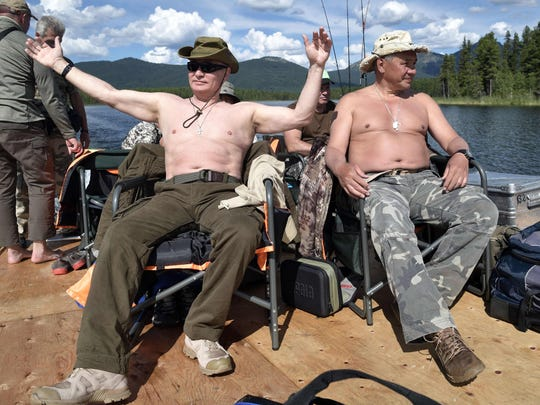 Russian President Vladimir Putin (L), accompanied by