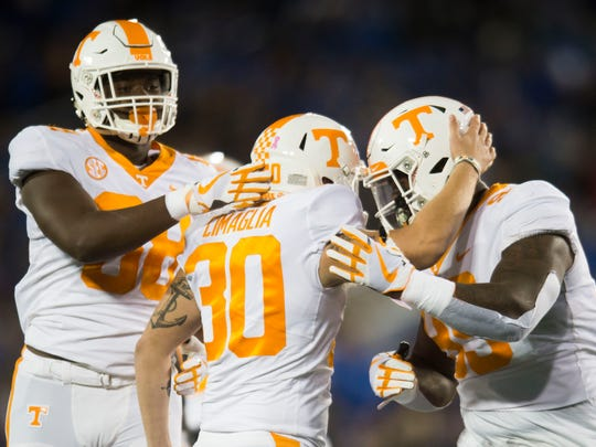Tennessee defensive lineman Reginald McKenzie Jr. (99) and Tennessee defensive lineman Brandon Benedict (88) congratulate Tennessee place kicker Brent Cimaglia (30) on his field goal during the Tennessee vs. Kentucky game at Kroger Field in Lexington, Kentucky Saturday, Oct. 28, 2017.