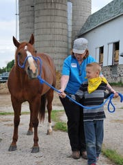 Beth Zarnke teaches a child how to lead a horse during AgriVenture at Memory Lane Farm.