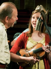Bobby Hicks encourages a fellow fiddler during one