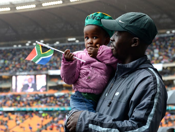 Tshepo Ledwaba holds his daughter Tshegofatso, 3, during the memorial service for former South African President Nelson Mandelaat the FNB Stadium in Johannesburg on Dec. 10. Mandela died Dec. 5. He was 95.