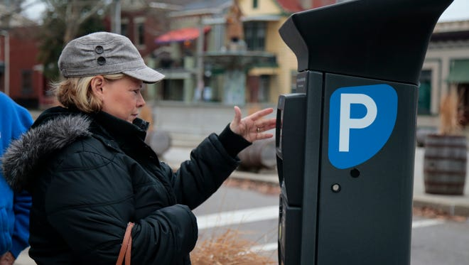 Barb Welbers, of Ludlow, Kentucky, pays for parking at one of the kiosks along Main Street, Friday, Jan. 13, 2017, in Covington, Kentucky.