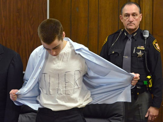 In this Tuesday, March 19, 2013, file photo,  T.J. Lane unbuttons his shirt during sentencing in Chardon, Ohio. Ohio police said Thursday, Sept. 11, 2014, that Lane, 19, the convicted killer of three students at a high school cafeteria, escaped from prison  but was recaptured.
