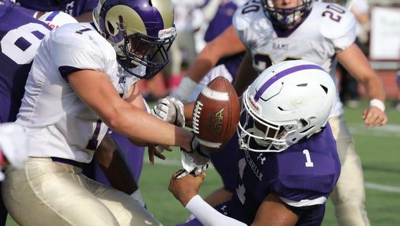 New Rochelle quarterback Jonathan Saddler has the ball