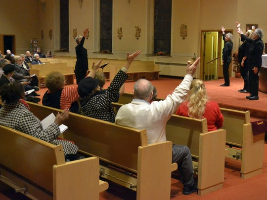 Attendees in the pews join members of Sign the Good News Deaf Choir from St. John the Evangelist Parish in Green Bay as they perform a song with sign language during the annual interfaith Thanksgiving worship service at St. Mary of the Angels Parish in Green Bay.