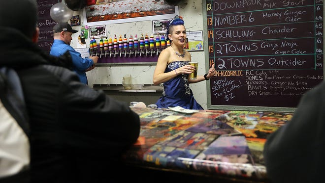 """Dressed in a prom dress in celebration of her 30th birthday, Ashley Martinez serves up a pint of beer to customers during a """"Nerdy 30"""" party at the pub."""