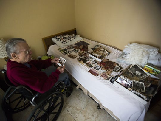 Jimmy Valentine looks over photos of his wife, Mary